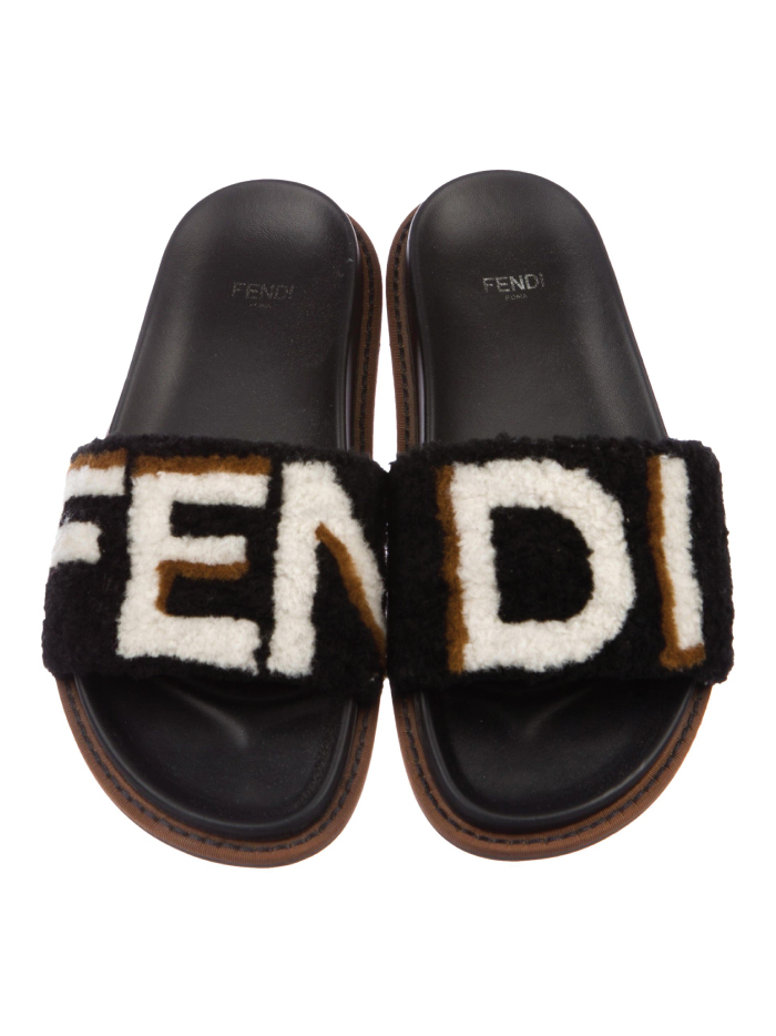 Out With The Slippers, In With This Spring Shoe Trend: Black logo shearling slides from Fendi.